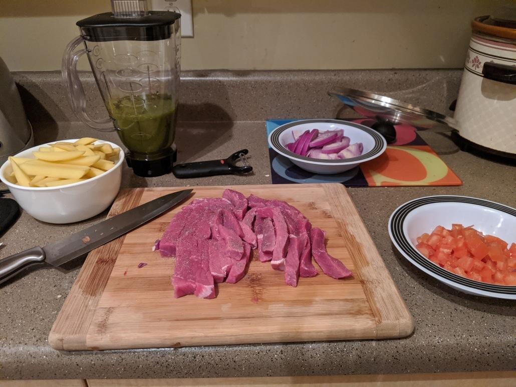 Prepared steak, onion, tomato, and potato.