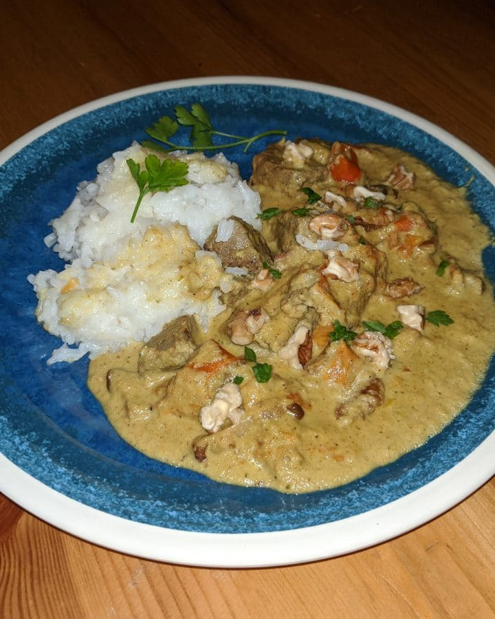 Beef korma with a parsley and walnut garnish, white rice on the side