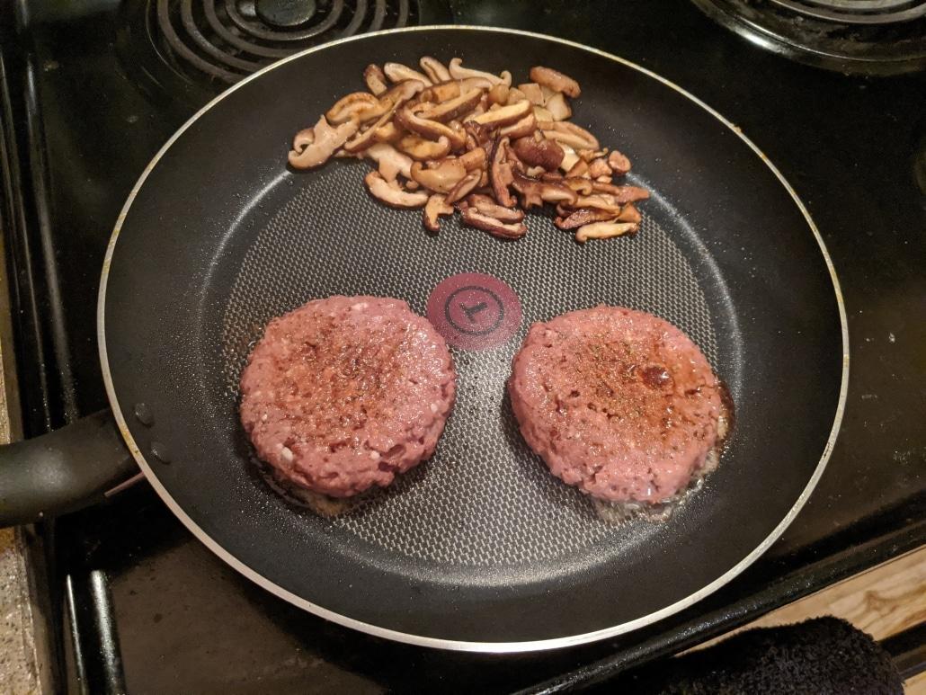 Cooking vegan burgers and mushrooms.