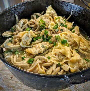 A cast iron pot filled with wonton egg noodle soup