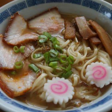 A bowl of Kitakata ramen, with naruto fish cake, scallions, menma, and char siu pork belly